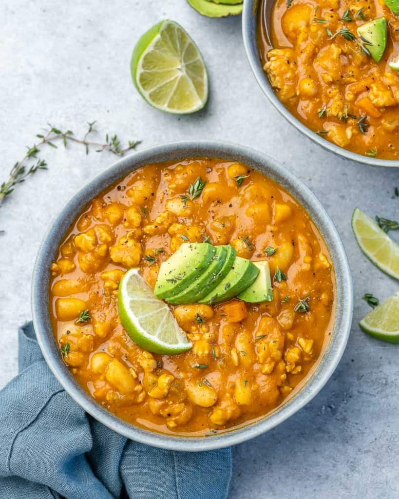 top shot of pumpkin chili bowl topped with lime wedges and avocado