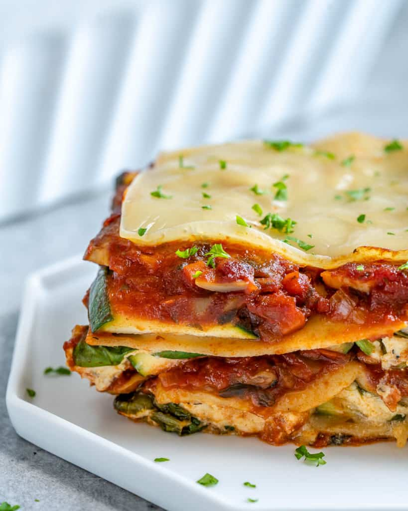 Close up view of slice of vegan lasagna with zucchini on white plate