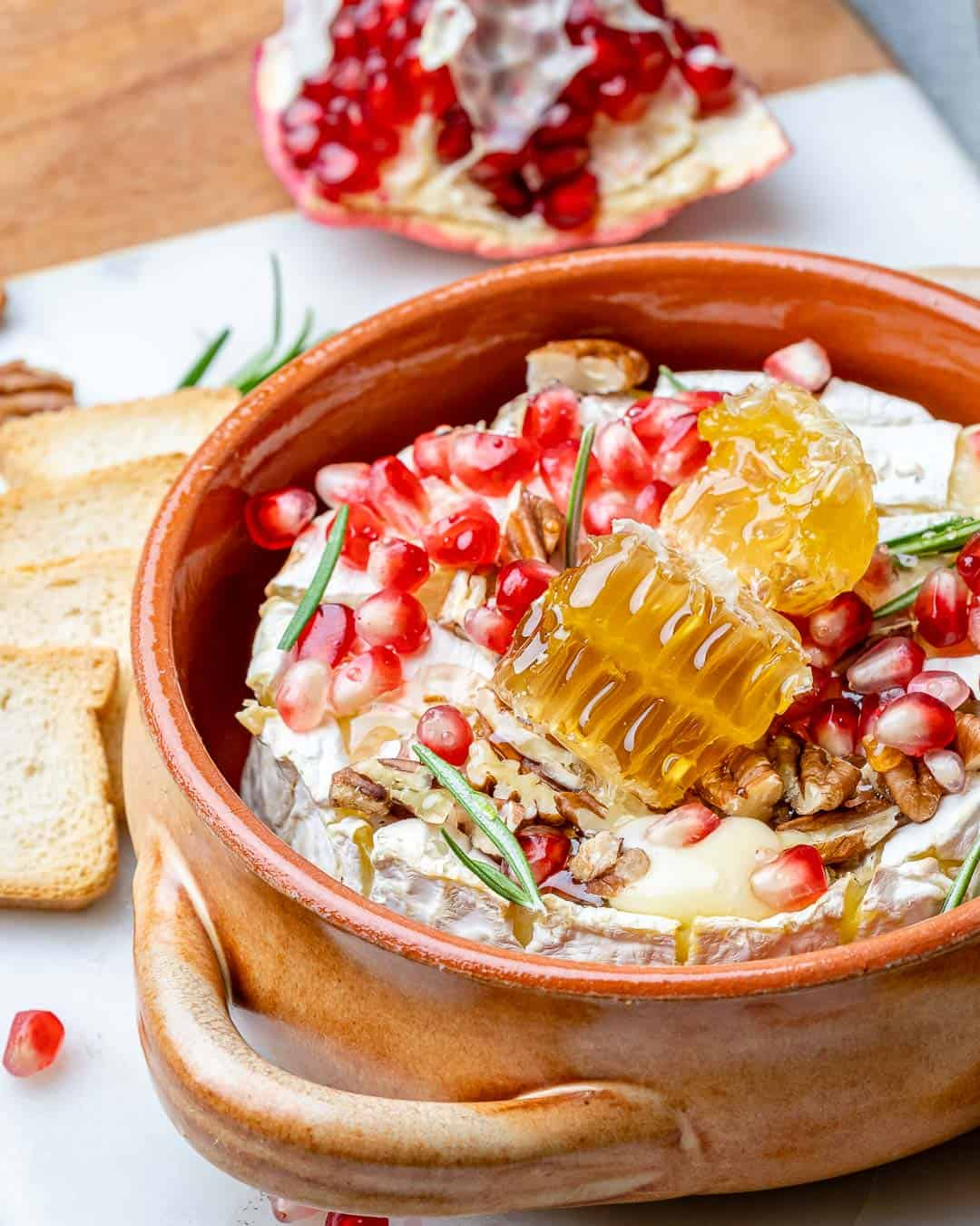 Baked brie with pomegranates in baking dish with crackers on side