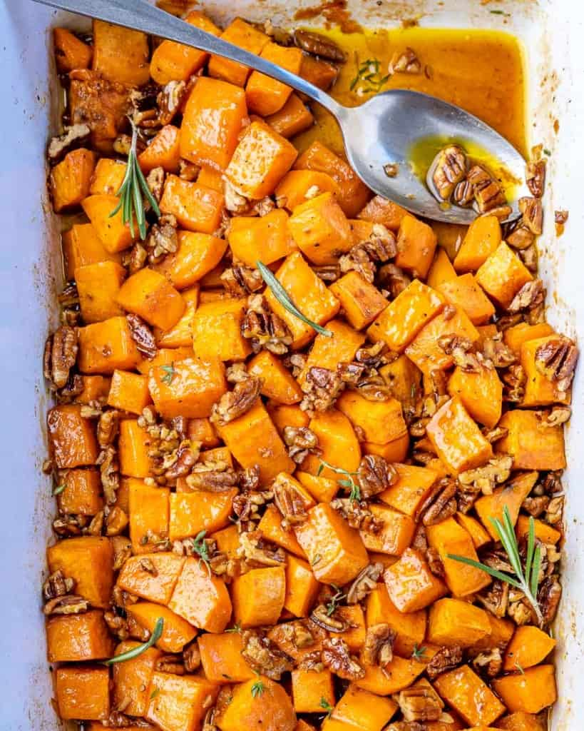 Top down view roasted sweet potatoes in a baking dish with a spoon.