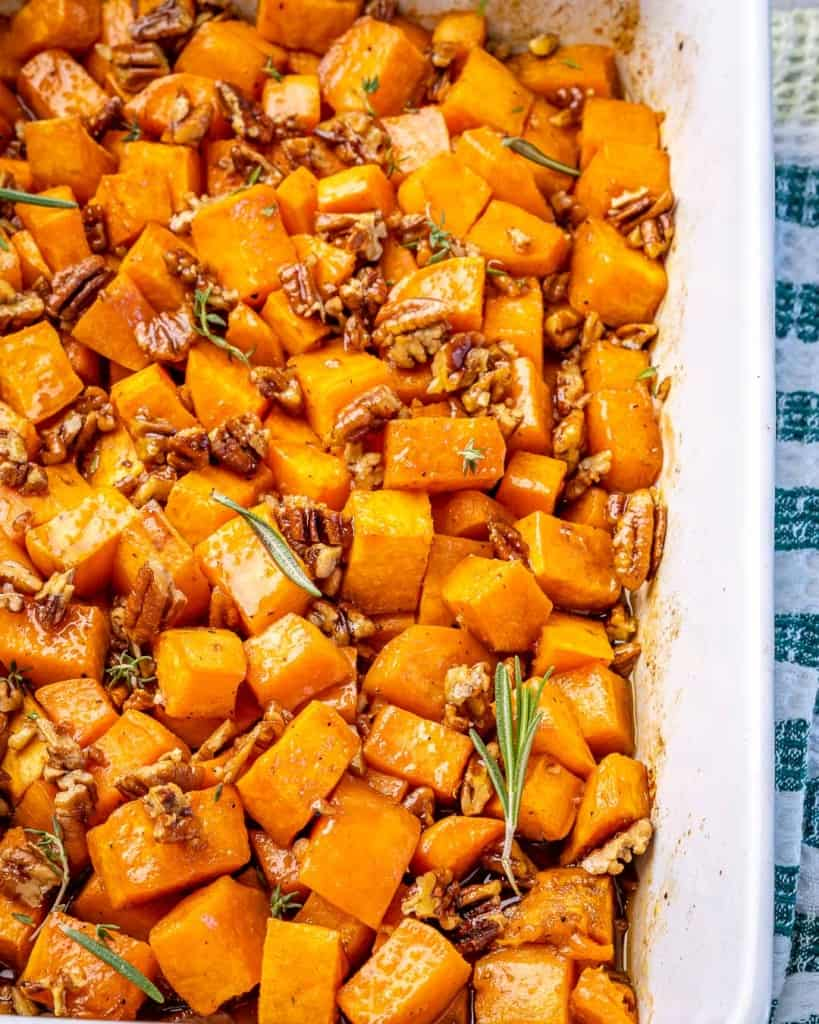 A white dish of roasted sweet potatoes on a cloth.