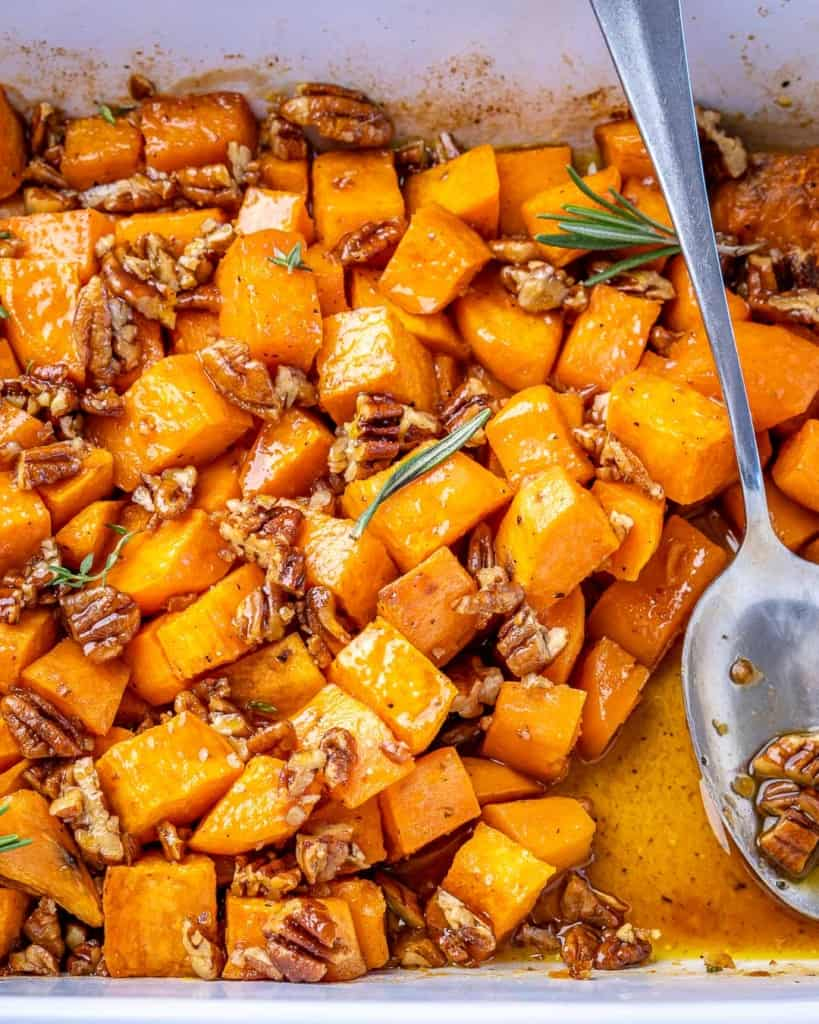 Overhead shot of maple roasted sweet potatoes in a white baking dish with a silver spoon.