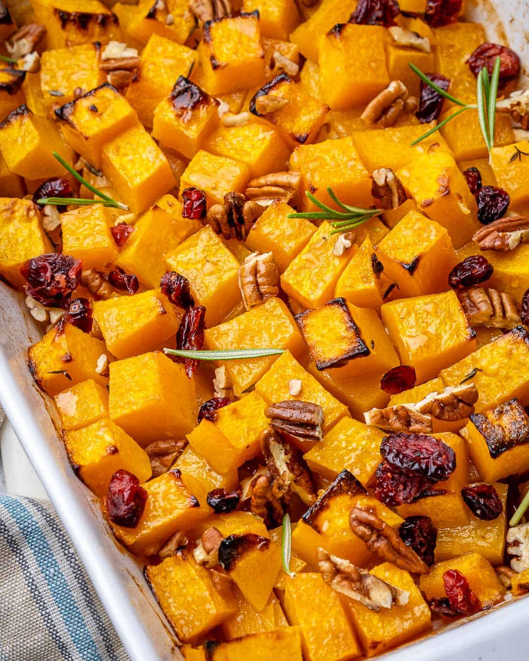 Close view of maple roasted butternut squash in white baking dish