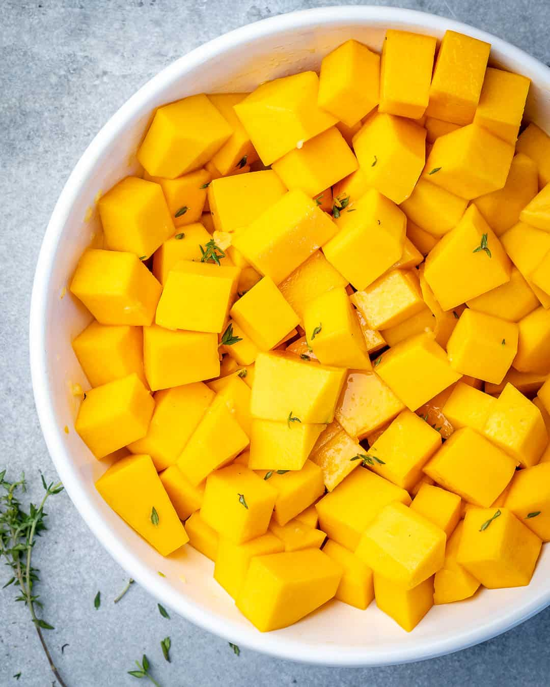 Butternut squash cubes in bowl covered in maple syrup and thyme sauce