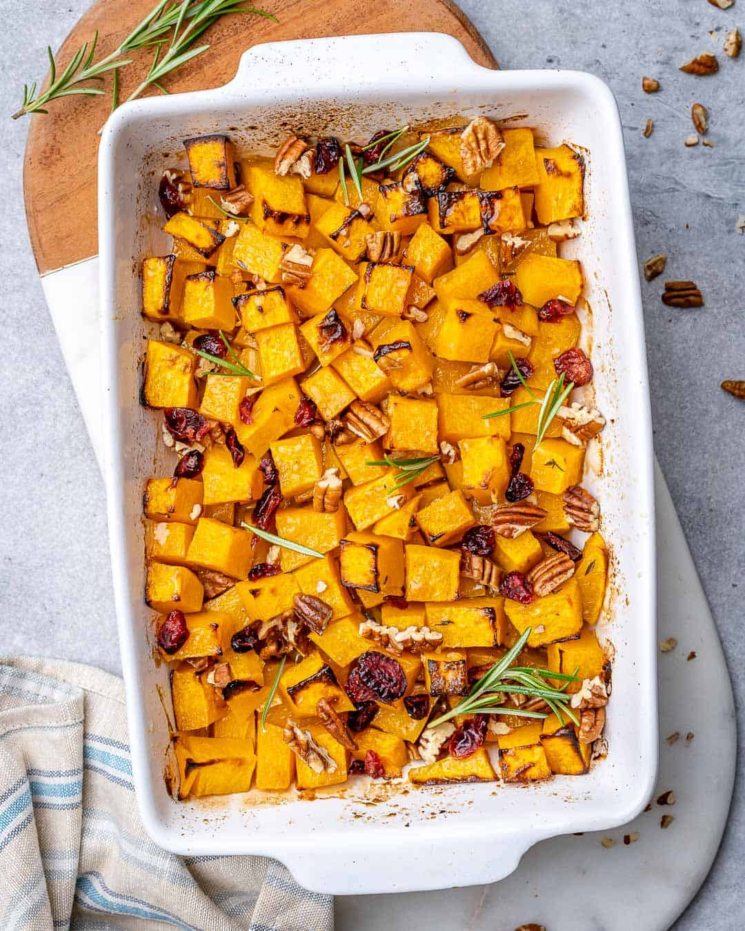 White baking dish with roasted butternut squash, pecans, and dried cranberries.