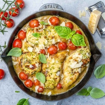 top view of pesto chicken and tomatoes in a black skillet with basil garnished
