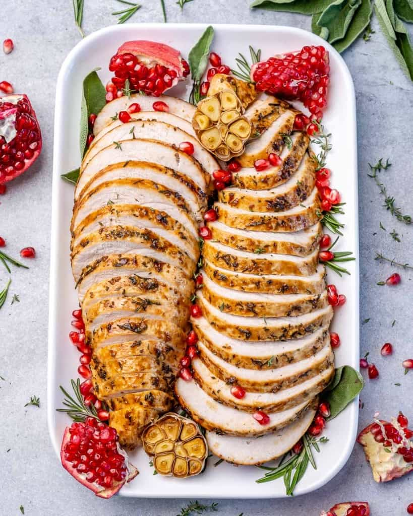 top shot of sliced turkey breasts with pomegranate garnishes