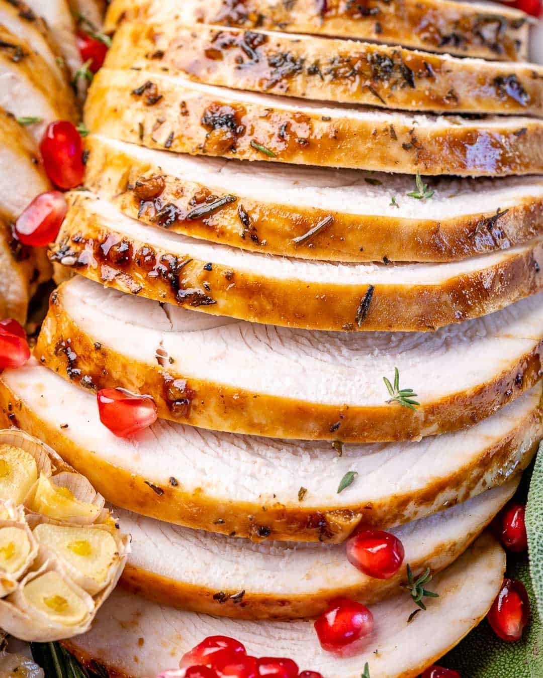 Close view of sliced turkey breast with pomegranate seeds sprinkled on top