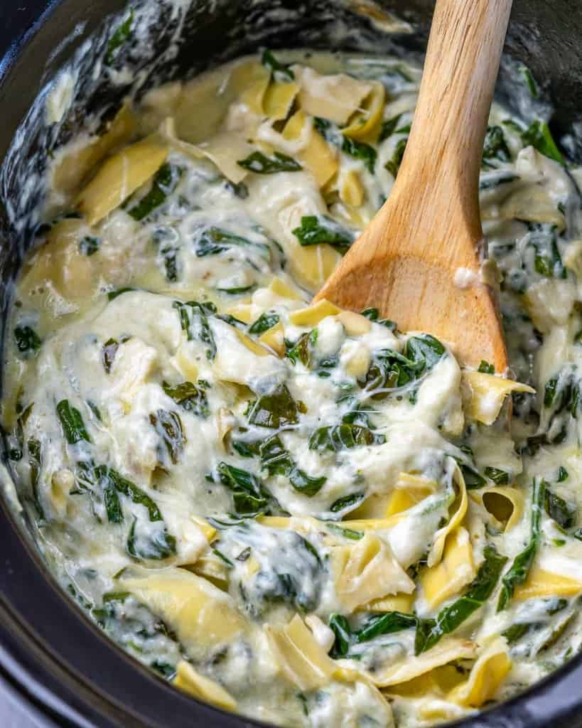 Overhead shot of spoon stirring spinach artichoke dip in a crockpot.
