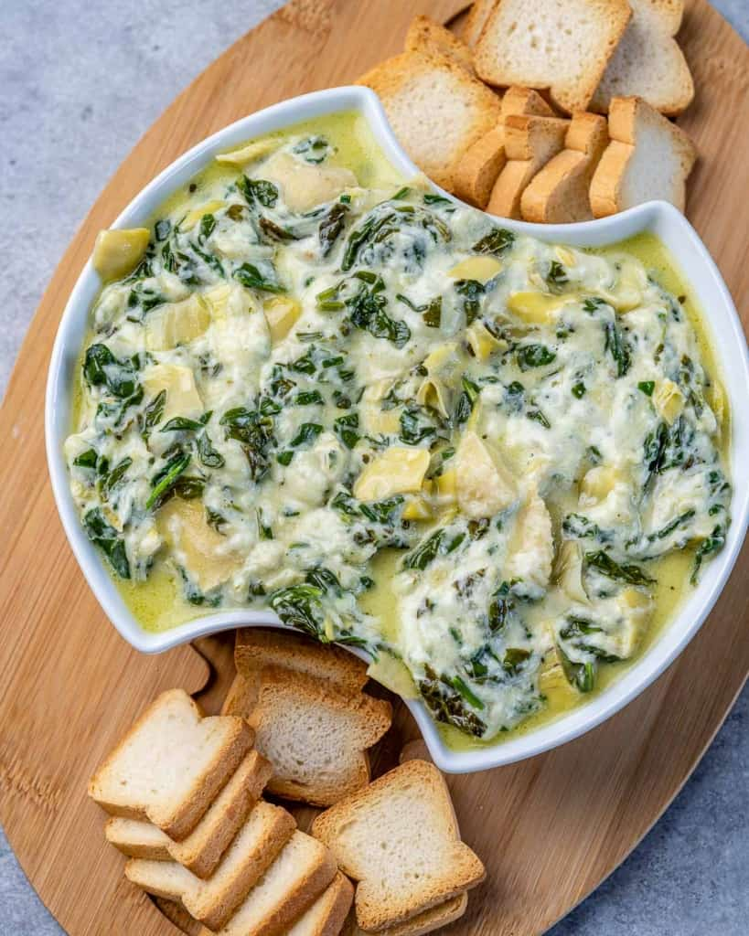 Overhead shot of spinach artichoke dip in a bowl on a wooden board.