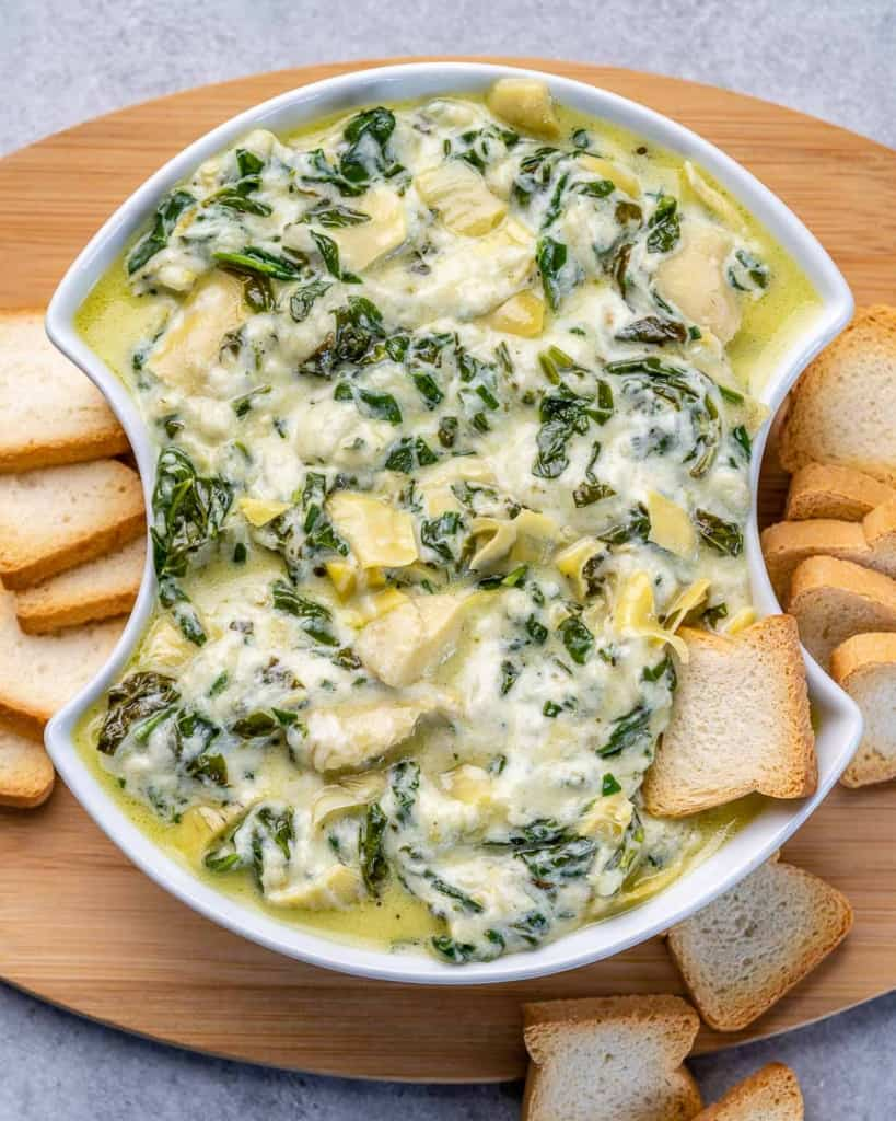 top view of spinach dip in a white bowl with slices of bread on the side