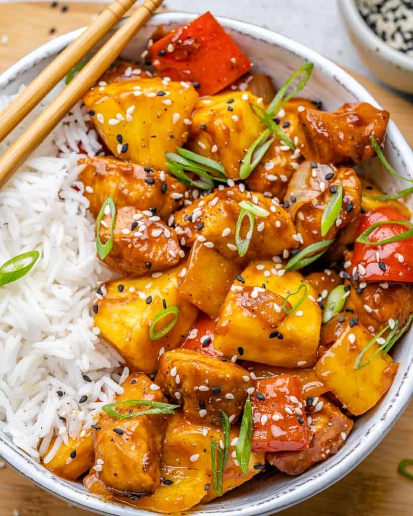 close up of sweet and sour chicken with rice in white bowl