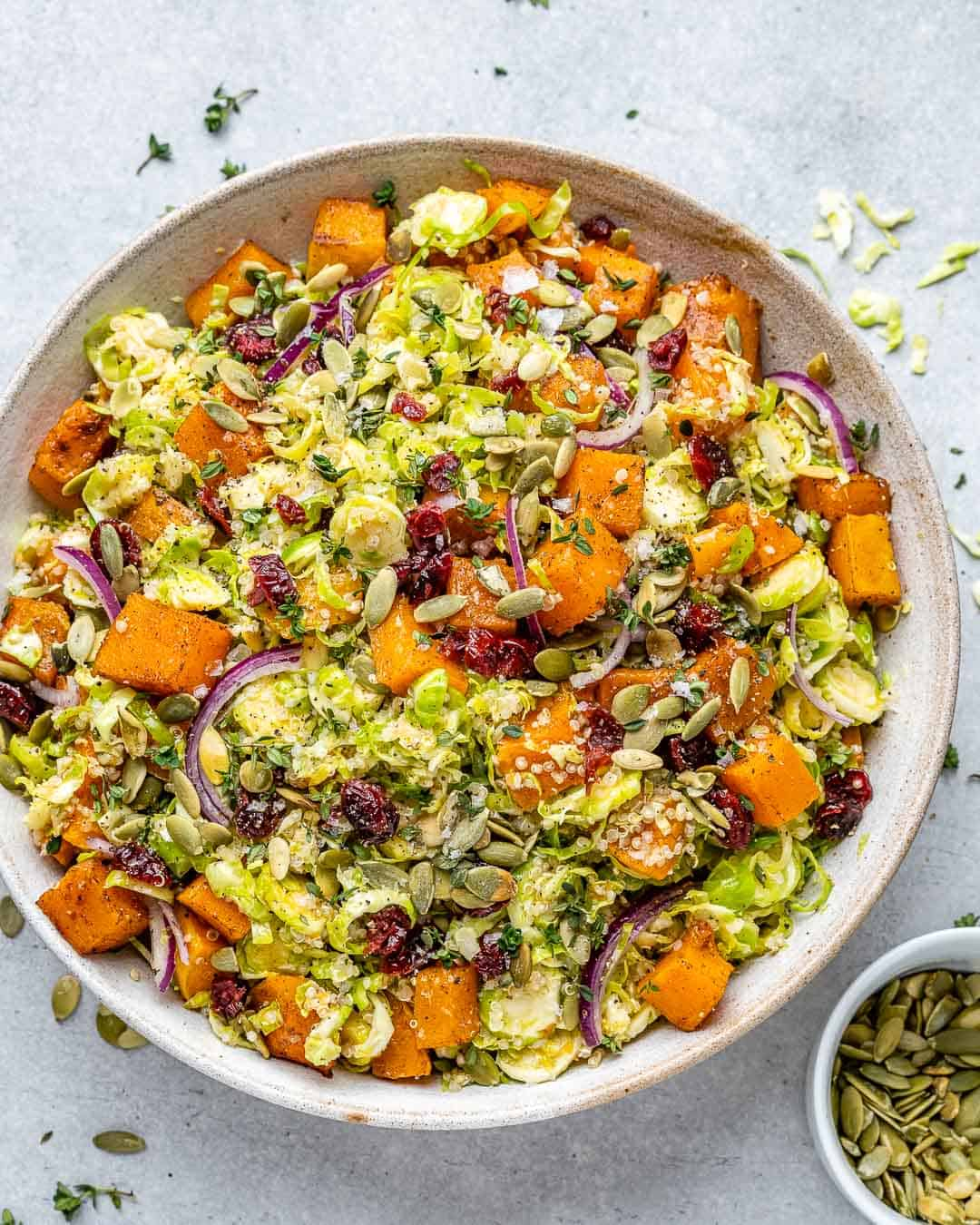 Overhead of bowl with roasted butternut squash and bowl of pumpkin seeds.