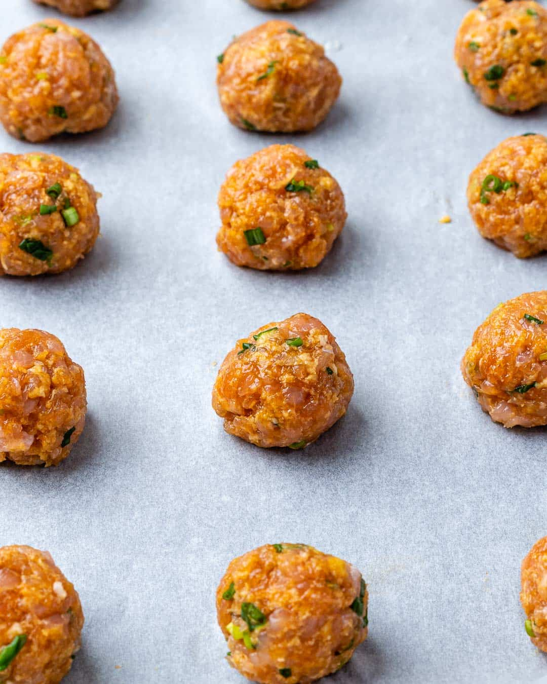 Formed meatballs on baking sheet before cooking.