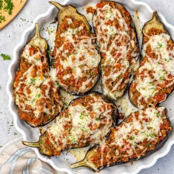 Top down view of eggplant with beef stuffing in a dish.