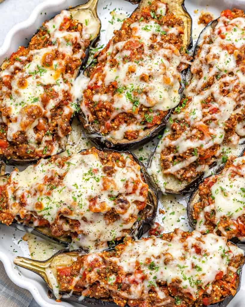 Top down view of stuffed eggplants in a dish.