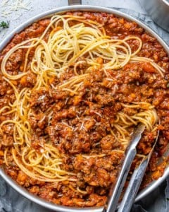 tongs in a pasta bolognese pan
