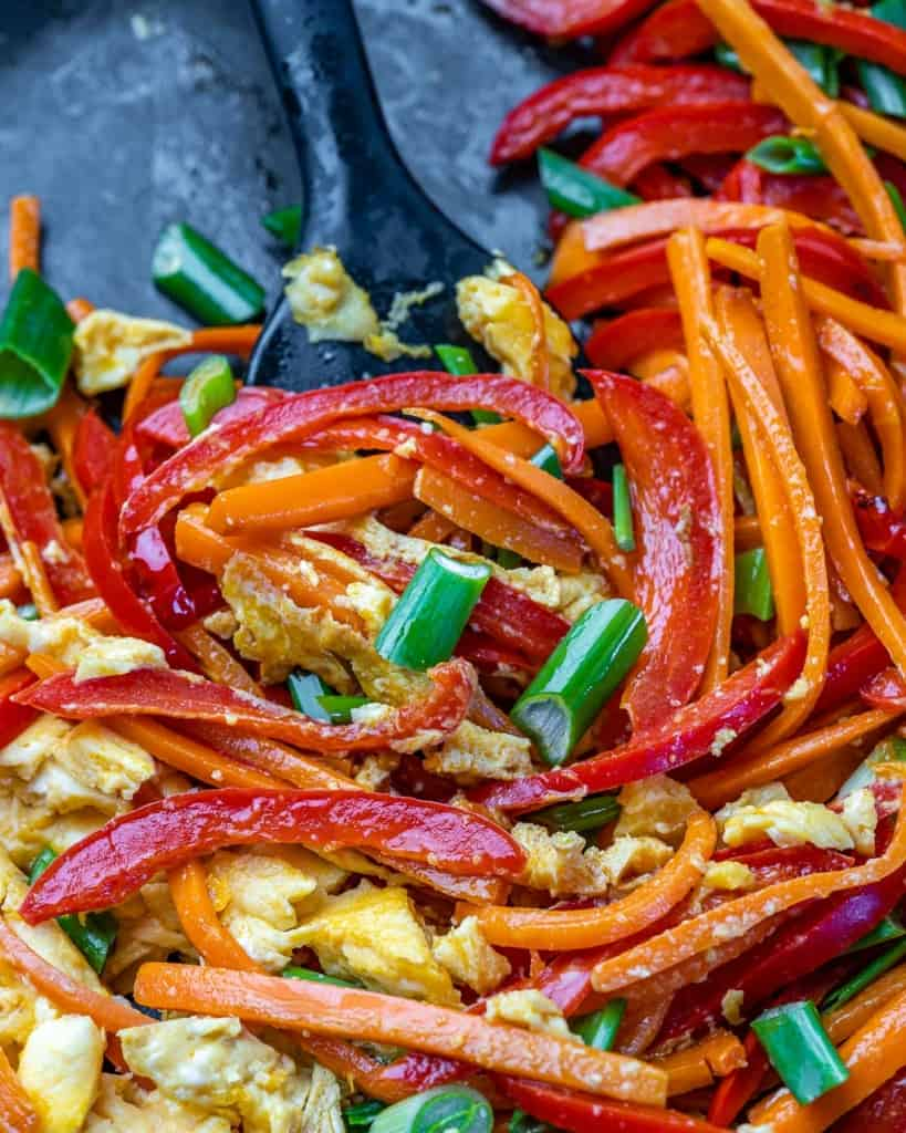 Close up of sautéd bell peppers, carrots, green onions, garlic, and scrambled egg.