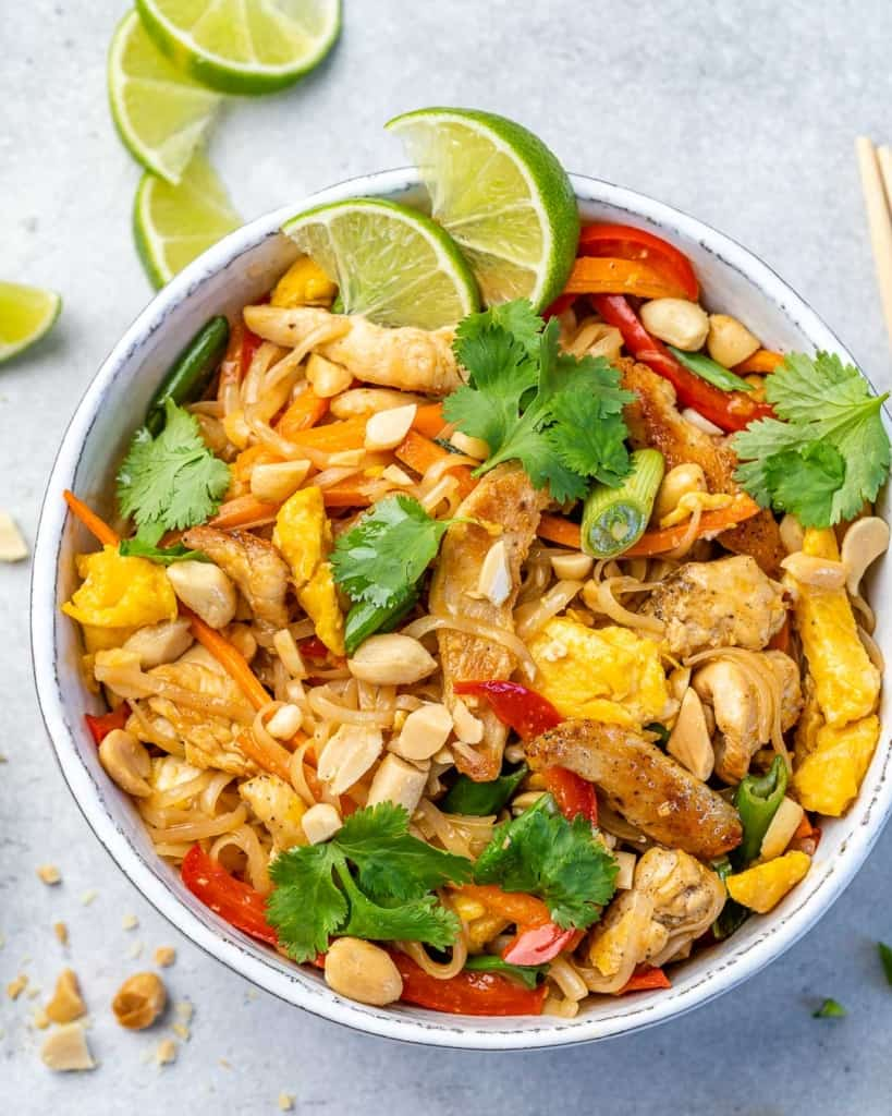 Overhead image of pad thai with chicken in a white bowl.