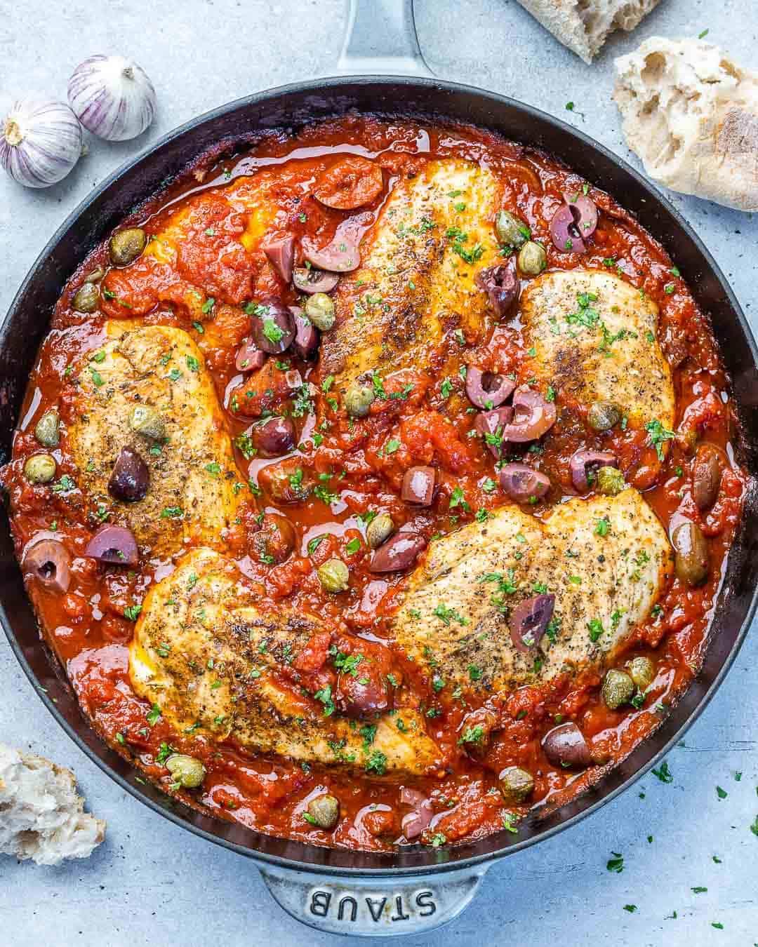 top view chicken puttanesca in black skillet