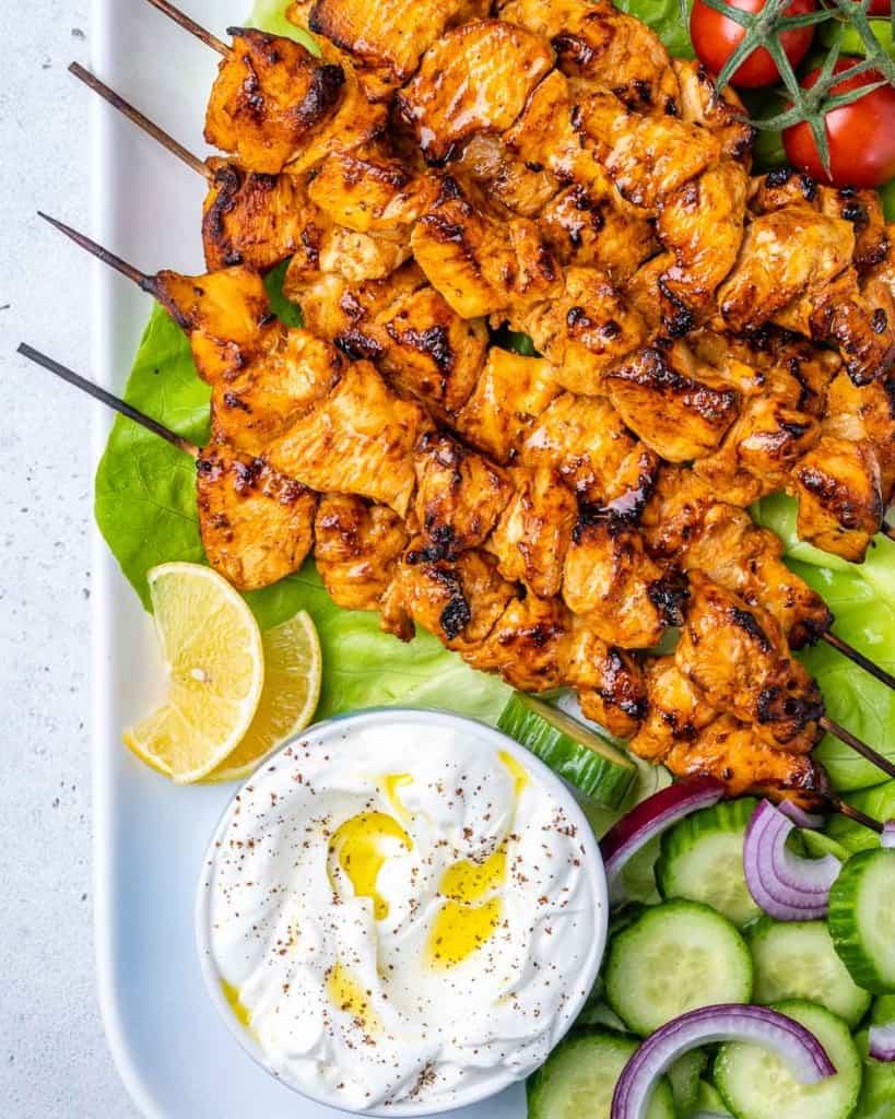 top view chicken kebabs with a side of yogurt dip