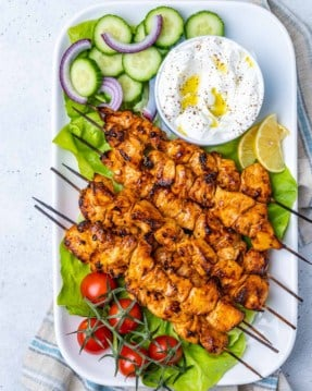 top view chicken shish tawook skewers on a long white dish