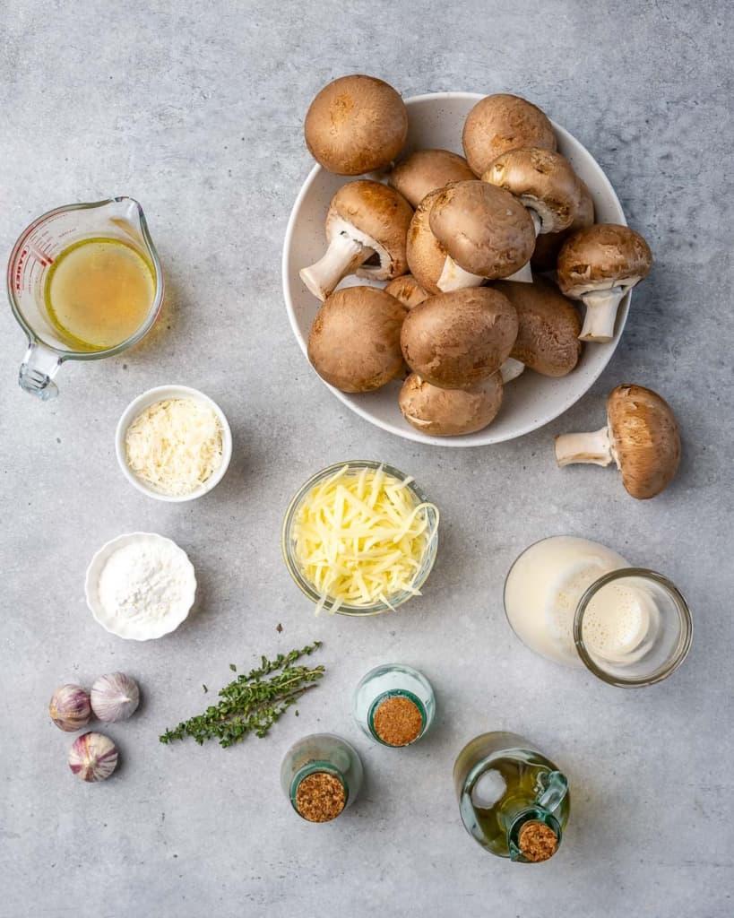 mushrooms, olive oil, garlic, chicken broth, cornstarch, almond milk, salt, pepper, mozzarella, Parmesan cheese, and thyme on grey surface