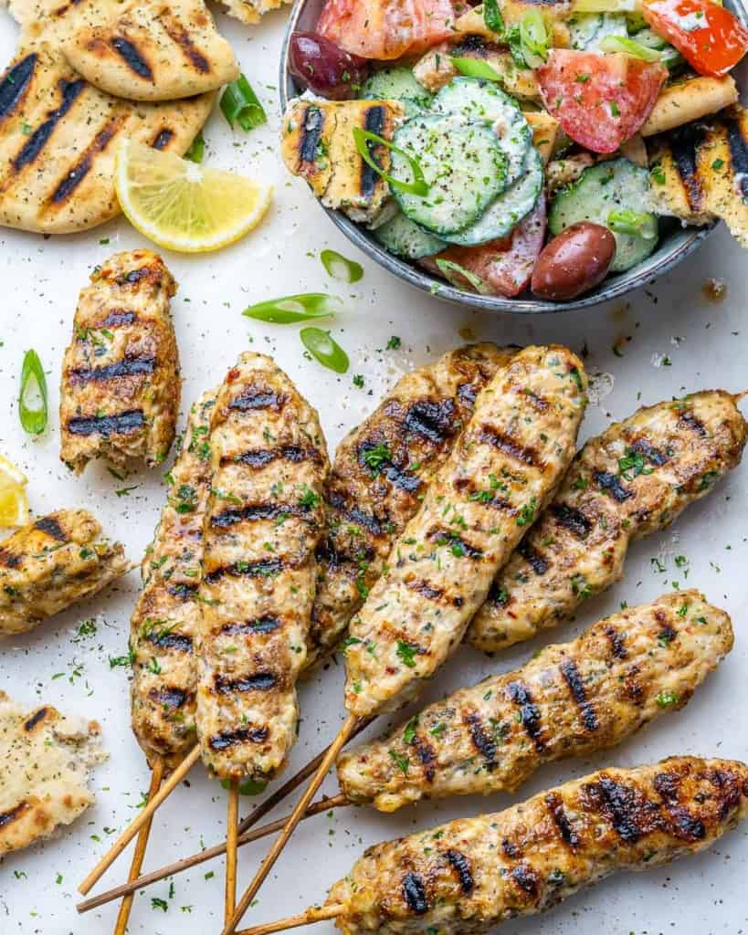 side shot of chicken kafta kebab next to salad bowl