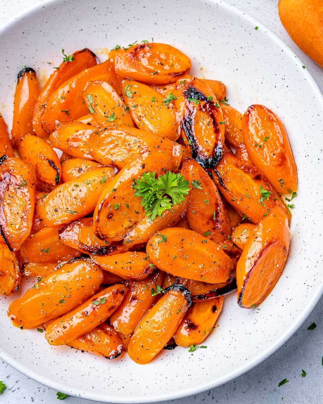 top view of glazed carrots in a white plate