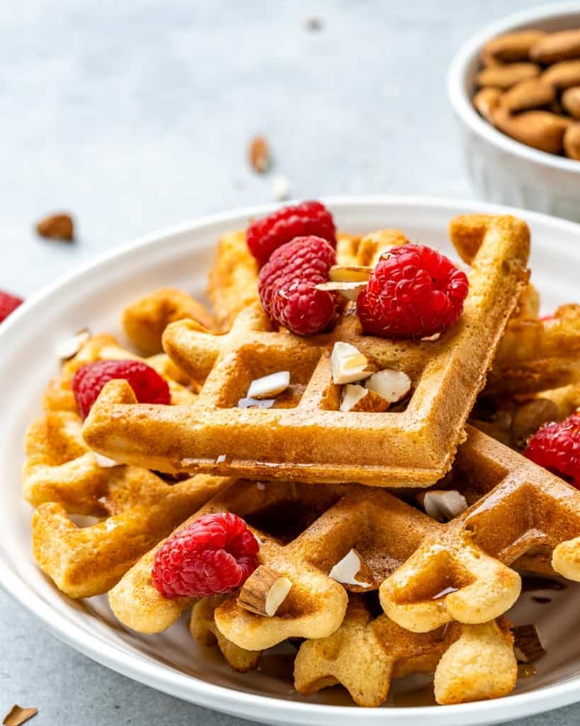 A white plate of keto waffles with almonds and berries on top.