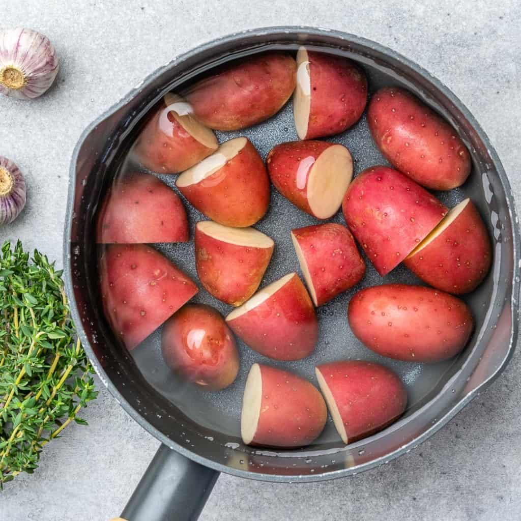 red potatoes halved in water to be par boiled