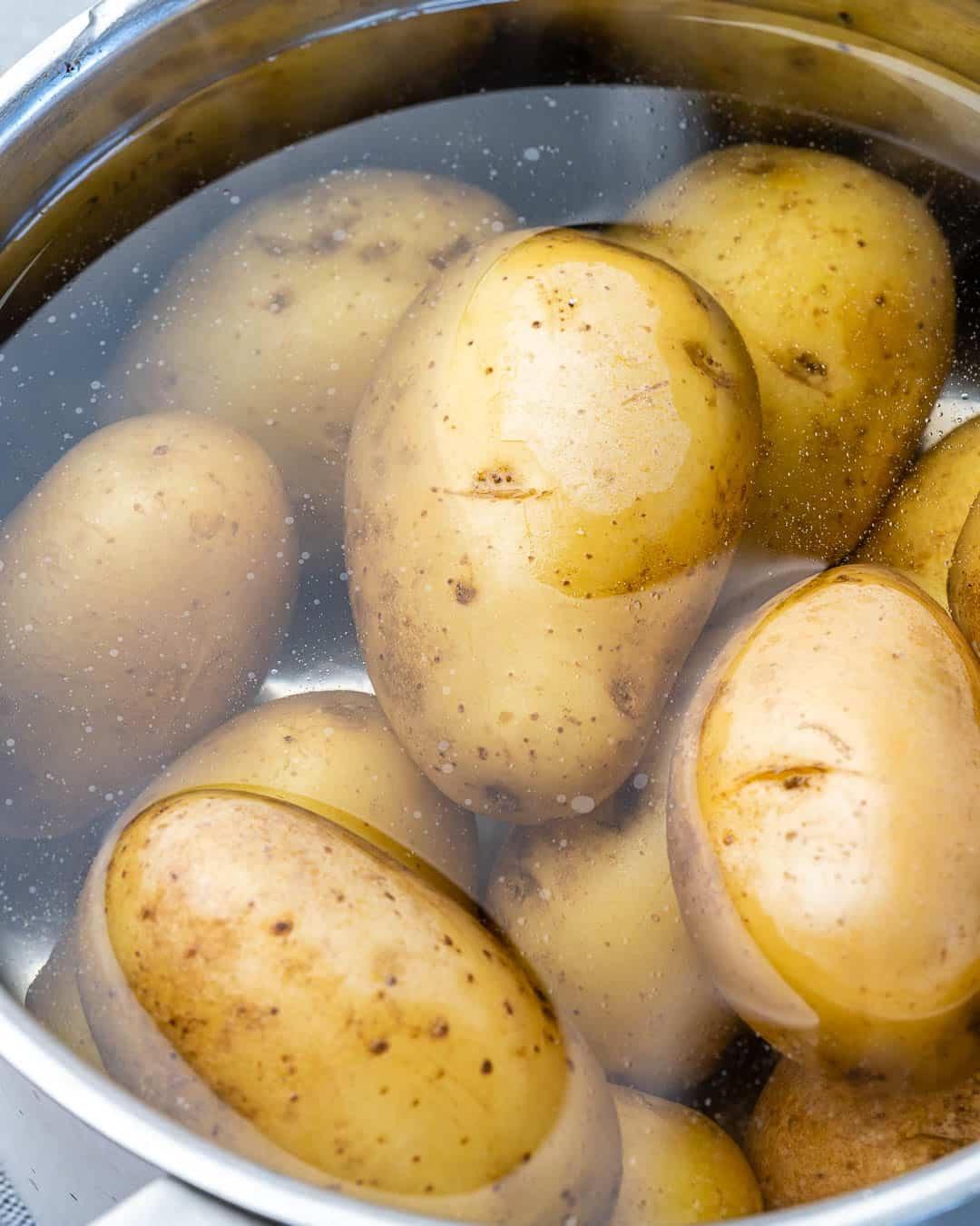 Potatoes in pot covered with water before cooking.