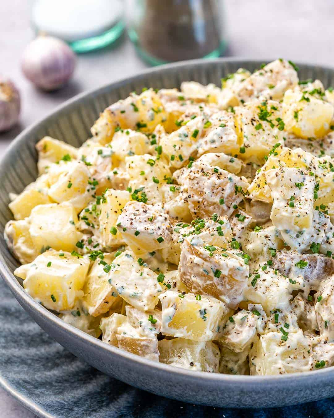 Bowl of healthy mustard potato salad with salt and pepper in background