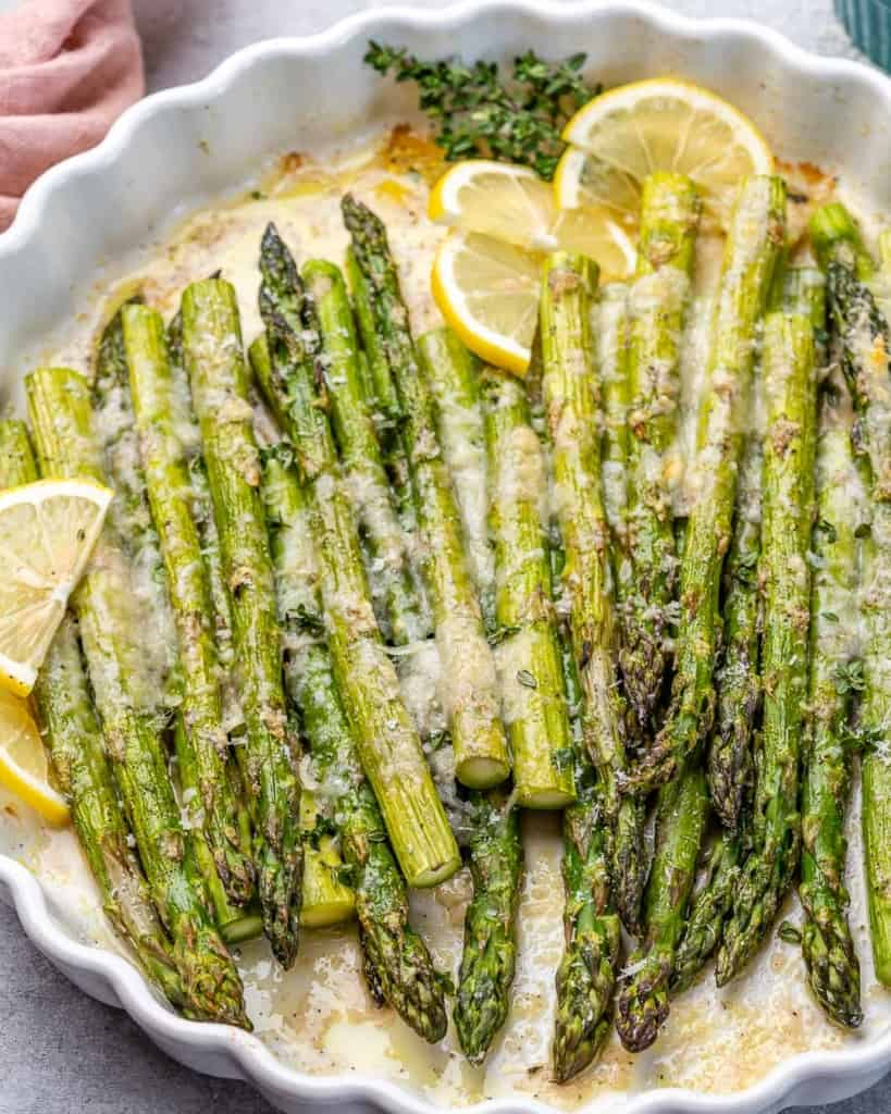 side shot of roasted asparagus on a white dish