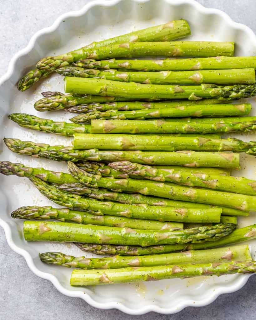 uncooked asparagus on a white dish