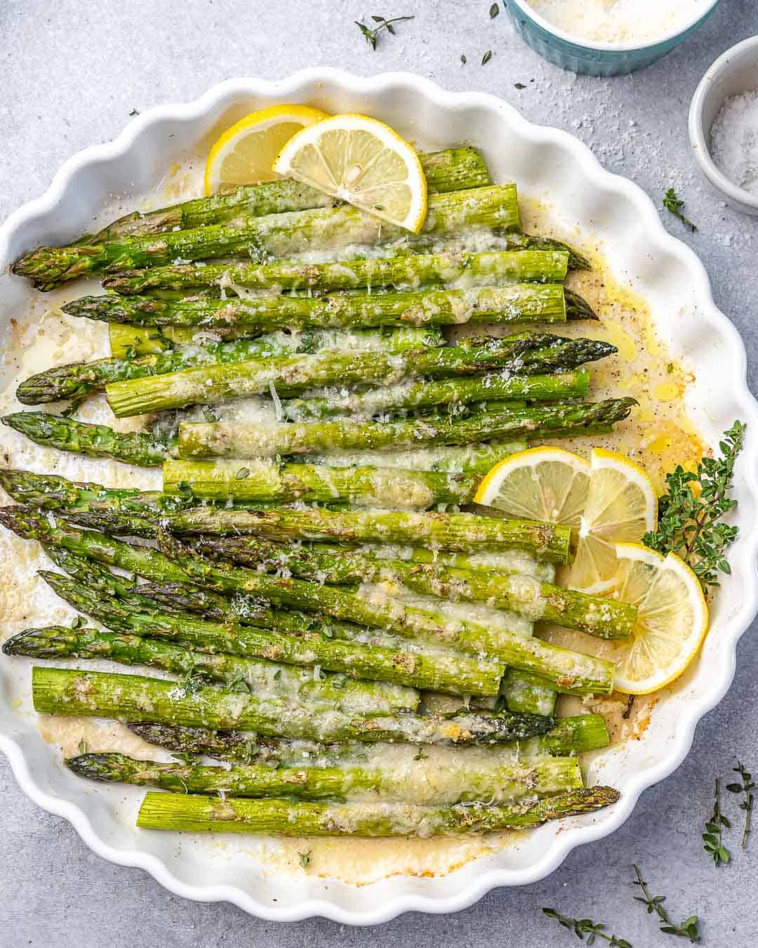 top view of baked asparagus in a white dish with lemon garnishes
