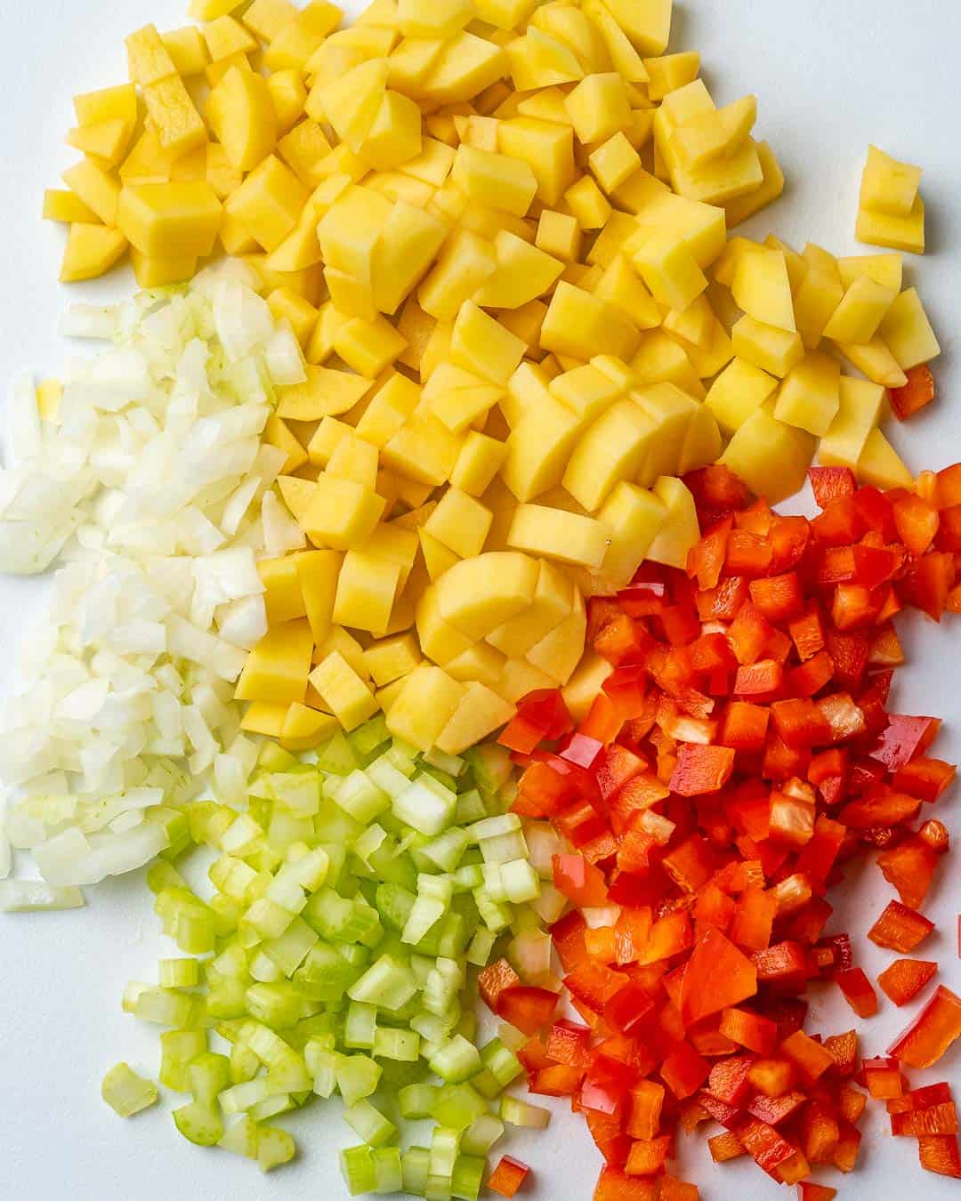 Corn, peppers, celery, and onion chopped on cutting board.