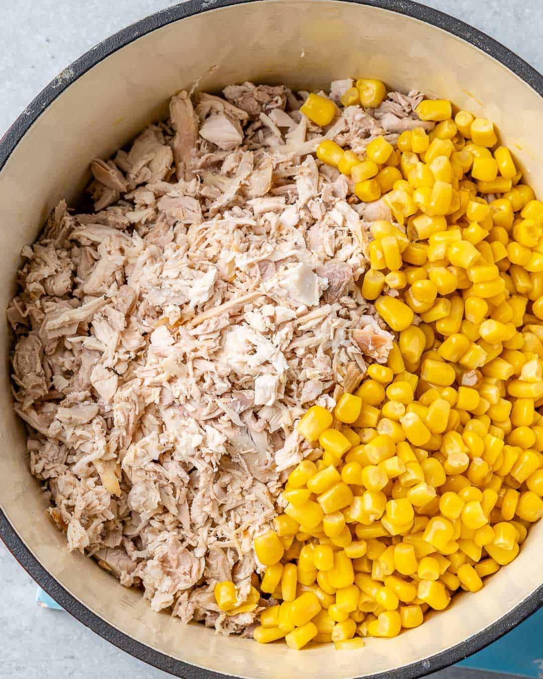 Shredded turkey and corn in pot.