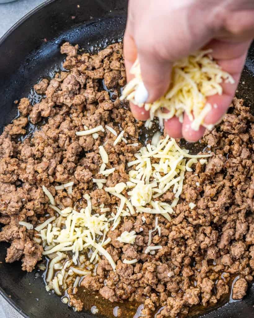 shredded cheese being added to ground beed