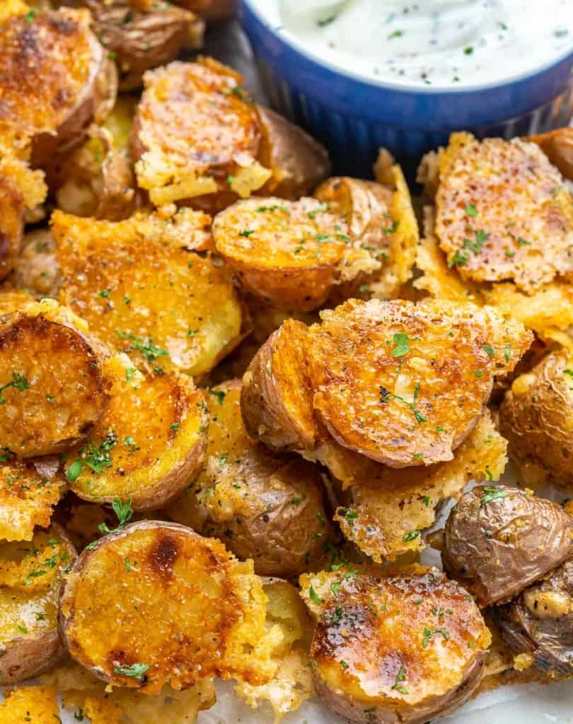 Close view of crispy potatoes on plate with dip