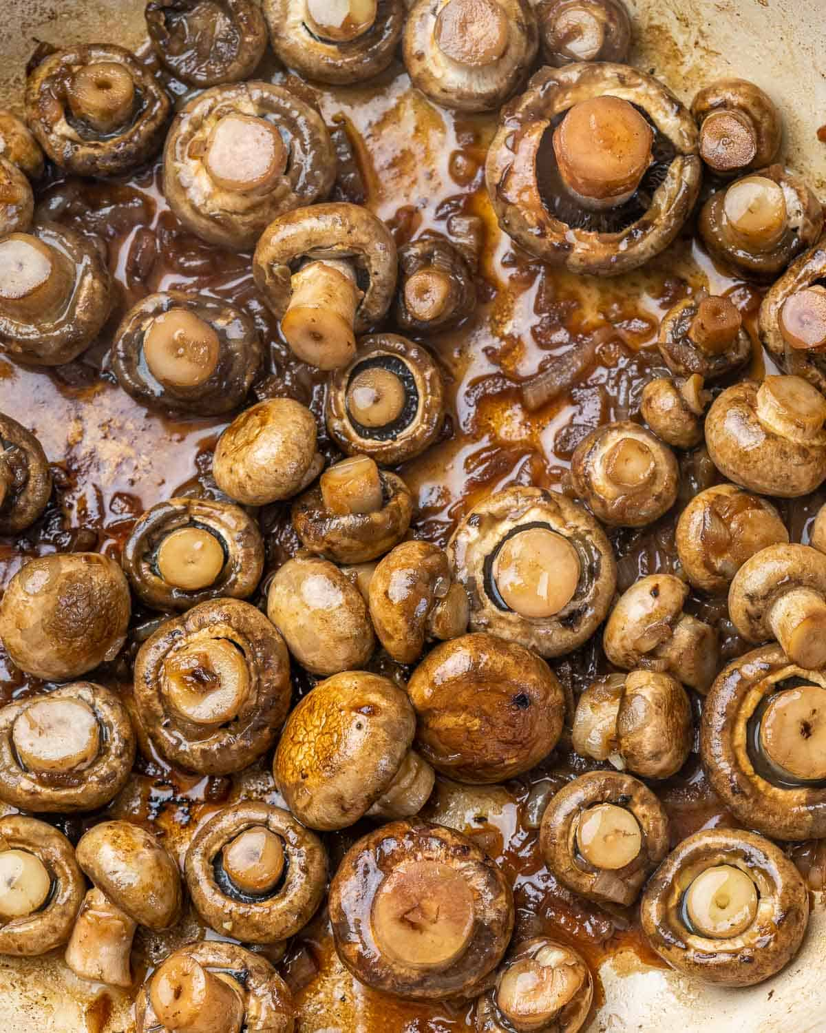 Mushrooms cooking in skillet with beef broth.