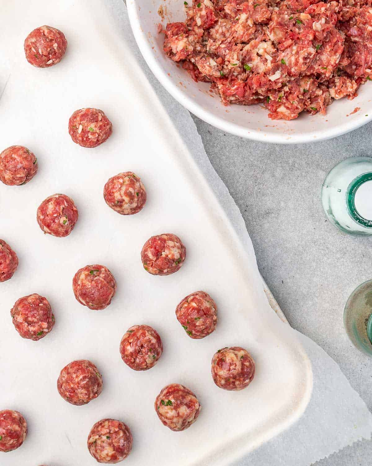 Meatballs formed on sheet pan with more meat in bowl.