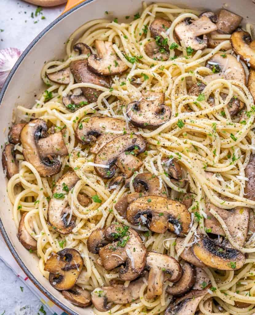 close up view of gralic mushroom spaghetti in a skillet