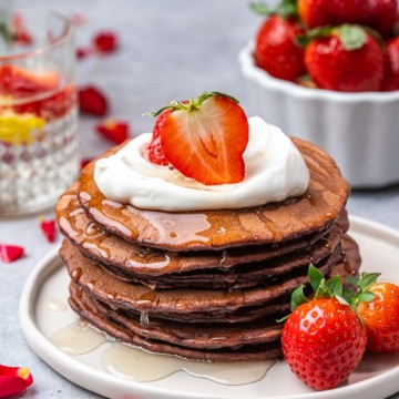 side shot red velvet pancakes with red roses in backgroundh