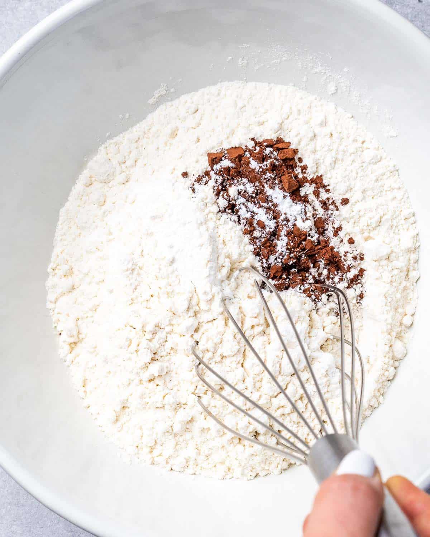 Whisking dry ingredients in white bowl.