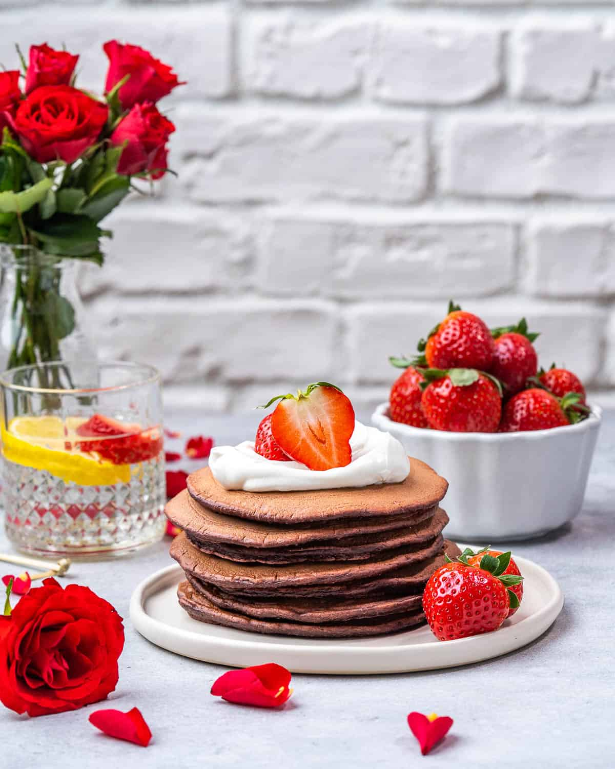 Red velvet pancakes stacked on plate with toppings.