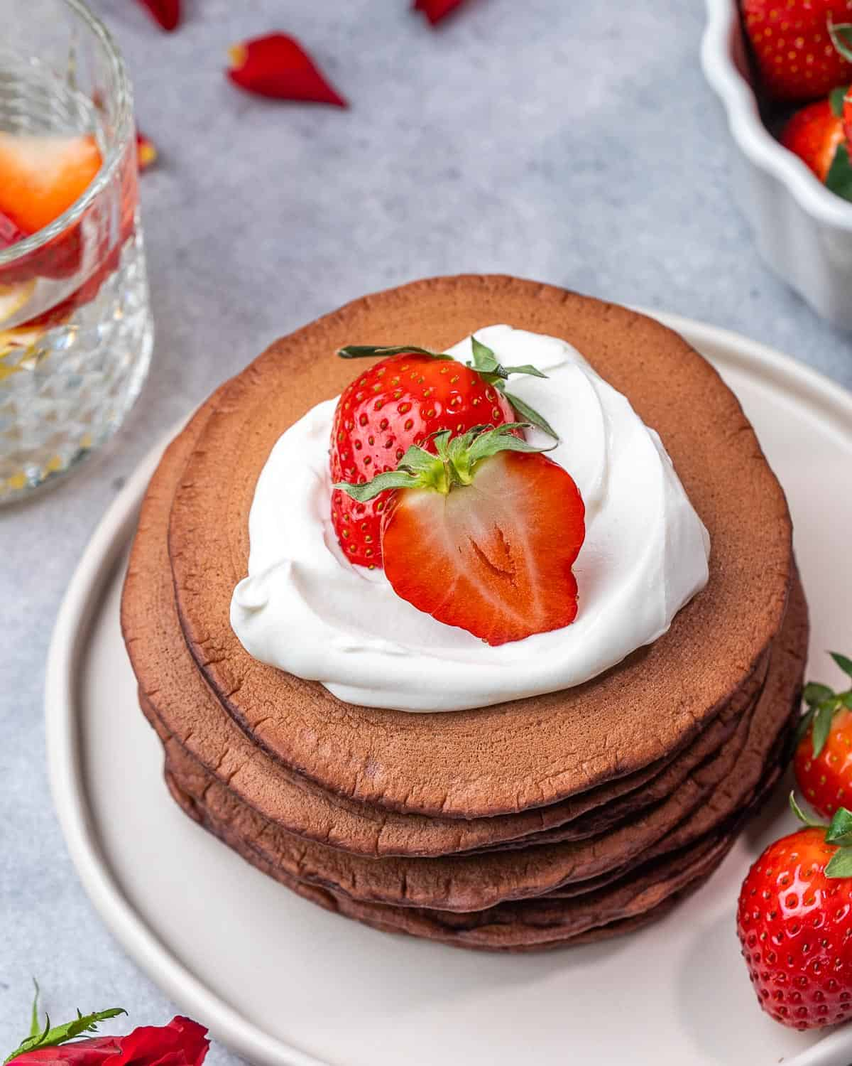 Top view of red velvet pancakes topping with cream cheese and strawberries.