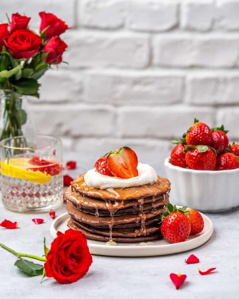 festive pancakes with roses and fresh strawberries next to pancakes