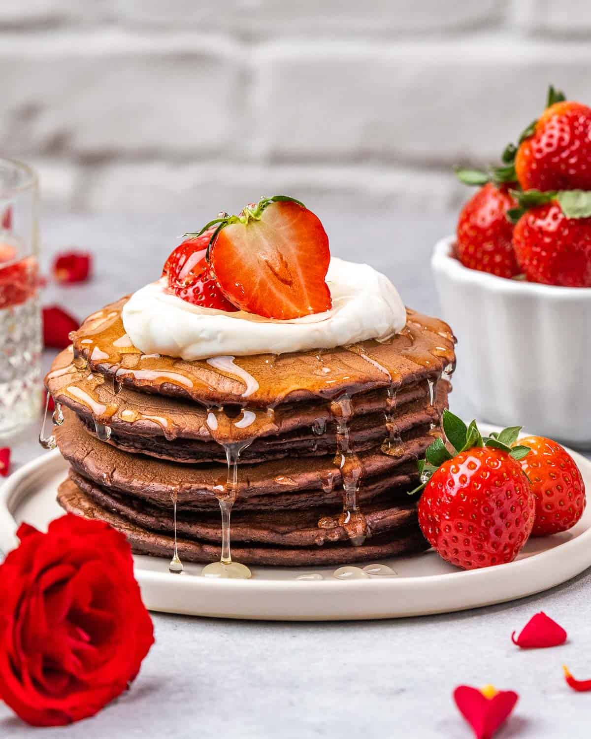 Pancakes stacked on plate dripping with syrup.