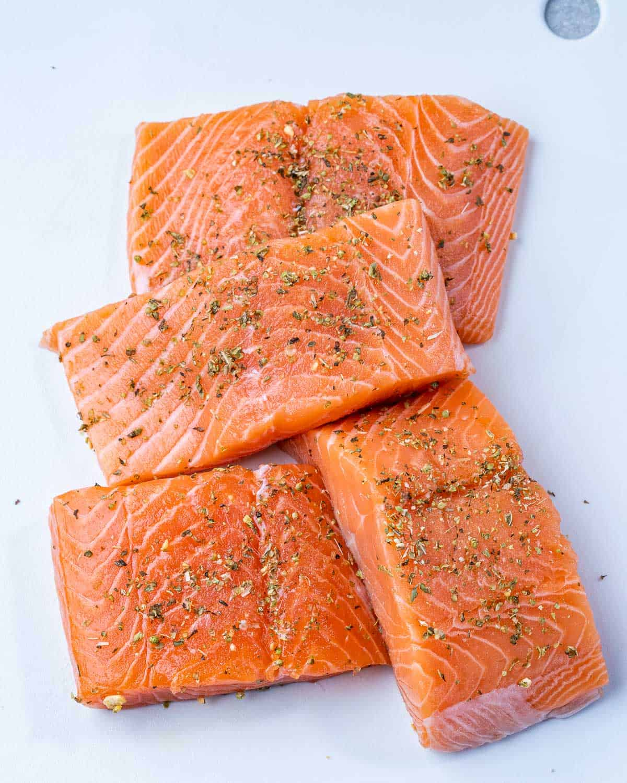 Four salmon filets seasoned on cutting board.